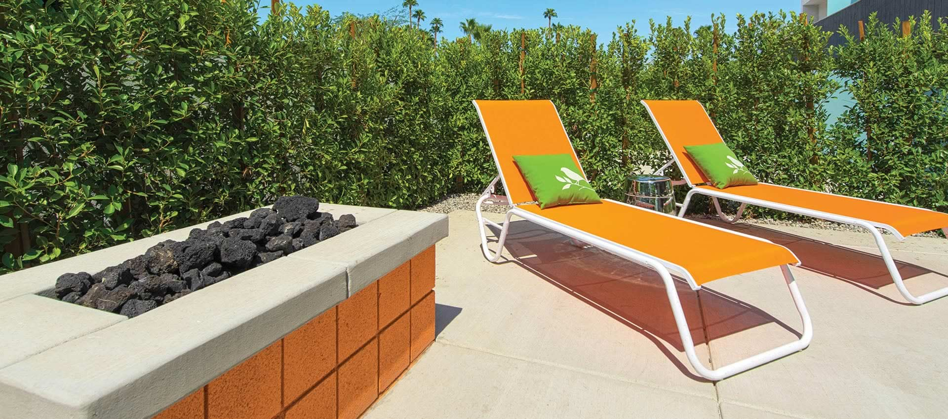 Orange lounge chairs by the outdoor firepit