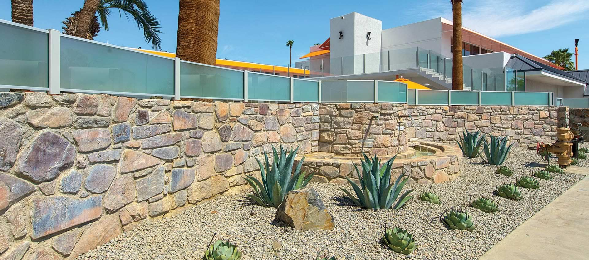 front of the hotel, the rock wall with cactus plants and palm trees