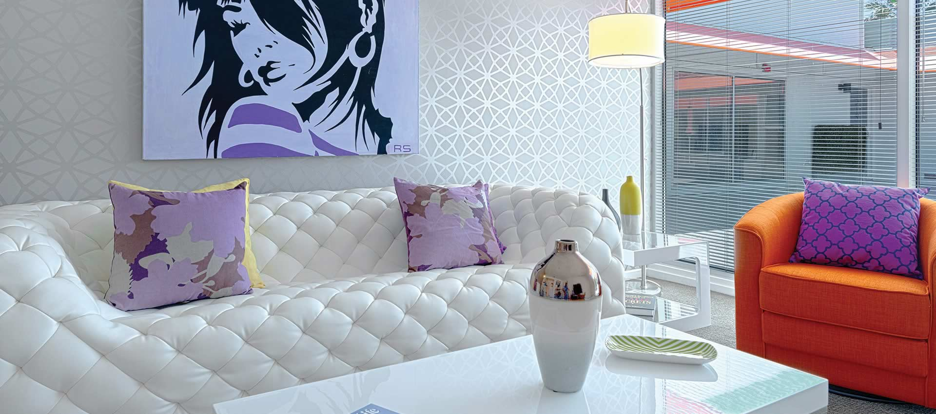 beautiful white couch and table in a room with windows looking outside patio