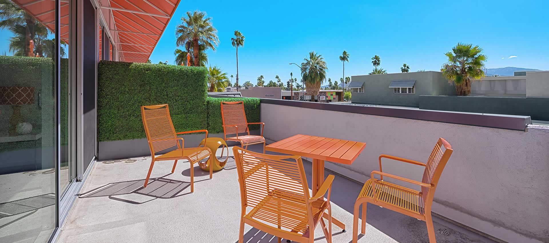 twist hotel room 222 patio with orange tables chairs palm trees